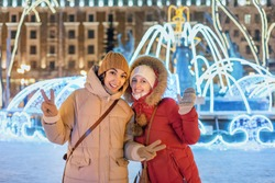 Girl friends having fun in city center decorated with lights and garlands for Christmas night and New Year holiday. Friendship and architecture concept