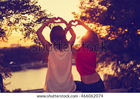 Girl-friends making a heart-shape for the sunset.