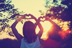 Girl-friends making a heart-shape for the sunset. Shallow depth of field on the hands.