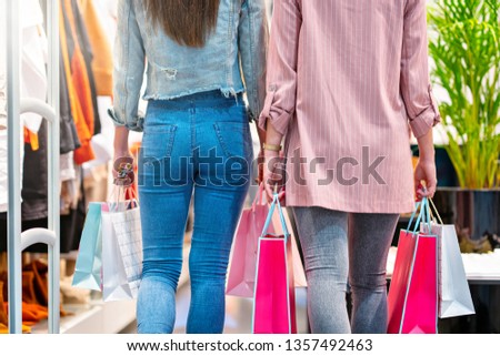 Girl friends shopping for clothes in store #1357492463