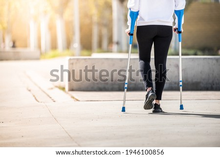 Girl from back with crutches, walking alone. Woman with crutches. Crutches Stock photo ©