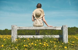 Girl from the back with sun hat sitting at wooden bench at yellow dandelion field