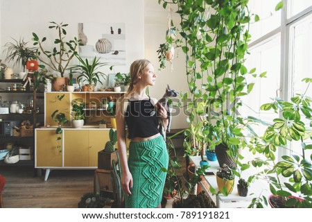 girl gardener with a cat in her arms looking out the window against a background of indoor plants #789191821