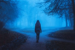 Girl goes on the road in a mysterious forest. Background for wallpaper. Strange forest in a fog with red leaves. Mystic atmosphere. Dark scary park. Paranormal another world.