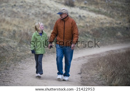 Girl granddaughter and  grandfather holding hands hiking walking on road trail, fun, happy.