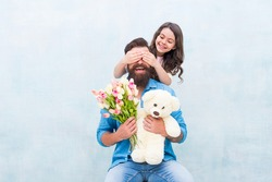 girl greeting dad with fathers day. happy family portrait with teddy bear. spring flower bouquet. womens day. prepare tulips for mothers day. daughter and father celebrate birthday. Spring mood.