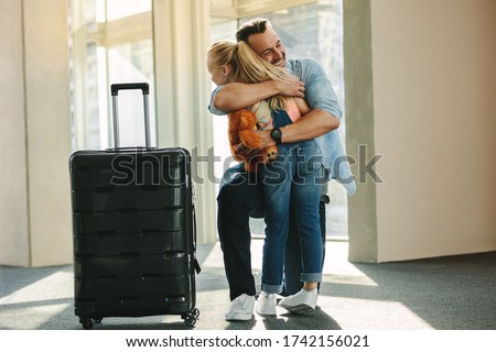 Girl greets her dad at the door when he arrives back from a trip. Daughter hugging her father just arrived from a business trip with a travel case.