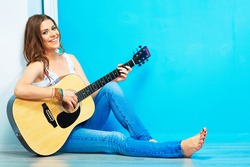 girl guitar play and sings . young model sitting on a floor. teenager style portrait.