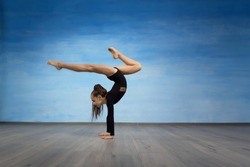 Girl gymnast in a black gymnastic swimsuit makes handstand on a blue sky background.
