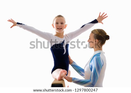 Girl gymnast on balance beam being taught by female teacher