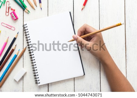 Girl hand drawing, blank paper and colorful pencils on white wooden table