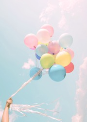 Girl hand holding colorful balloons. happy birthday party. vintage pastel filter effect