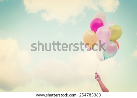 Girl hand holding multicolored balloons done with a retro vintage instagram filter effect, concept of happy birth day in summer and wedding honeymoon party (Vintage color tone)