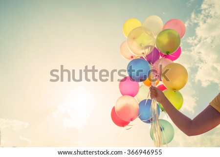 Girl hand holding multicolored balloons done with a retro vintage instagram filter effect, concept of happy birthday in summer and wedding honeymoon party (Vintage color tone)