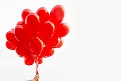 Girl hand holding red balloons on white
