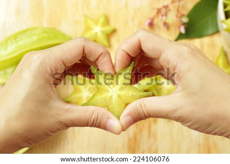Girl hand in heart form love with sliced star fruit. Healthy concept.