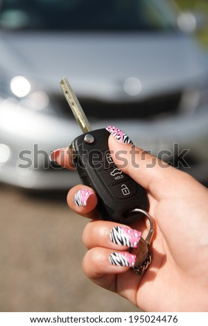 girl hand presses on the remote control car alarm systems
