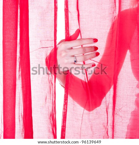 girl hand under the red curtain