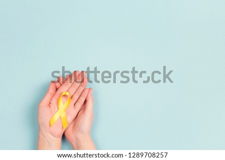 Girl hands holding Childhood Cancer Awareness Yellow Ribbon on blue background. Childhood Cancer Day February, 15.