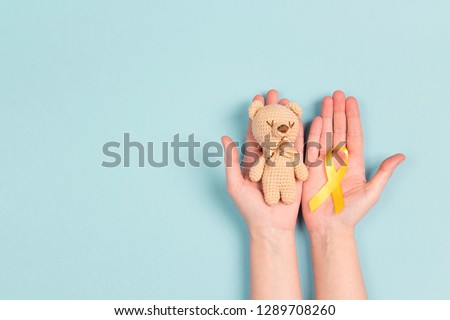 Girl hands holding children's toy with a Childhood Cancer Awareness Yellow Ribbon on blue background. Childhood Cancer Day February, 15.