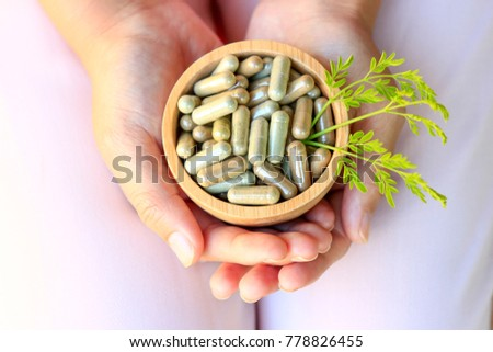 Girl hands holding herbal capsules in wooden bowl