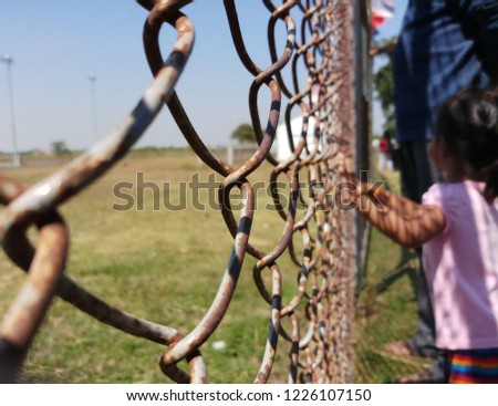 Girl hands holding wire fence #1226107150