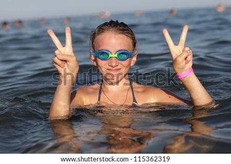 Girl hands show victory gesture in the sea, Rhodes, Greece