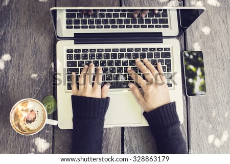 girl hands with cup of coffee, smartphone and laptop on a wooden table stock photo