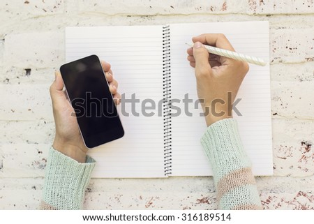 Girl hands with smartphone and blank diary with pen on a wooden table