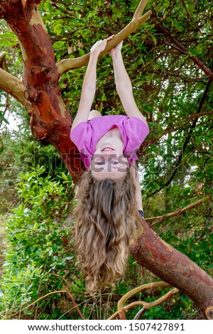 Girl hanging from a beautiful arbutus tree while her long wavy hair hangs down