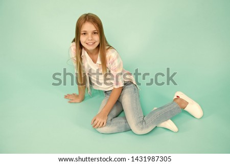 Girl happy face sit on floor attentive looking at camera turquoise background. Kid girl with long hair relaxing. Just relaxing here. Feel comfortable and freely. Time to relax. Find place to relax. #1431987305
