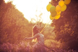 Girl have fun with yellow balloons at the sunset. Concept of freedom