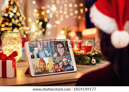 Girl having a Christmas video call with her happy family. Concept of families in quarantine during Christmas because of the coronavirus. Xmas still life with a tablet in a cozy room Foto stock ©