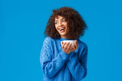 Girl having chat with girlfriend while drinking coffee. Cheerful and cute african-american lovely woman with afro haircut, in sweater, tilt head gazing left and holding hot cup delicious tea