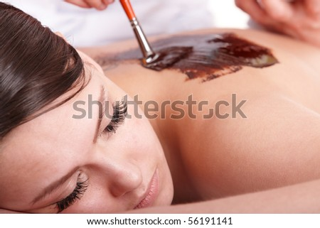 Girl having chocolate body  mask in  beauty parlour.