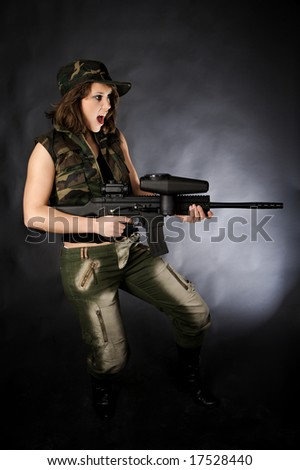 Girl having fun with paintballgun