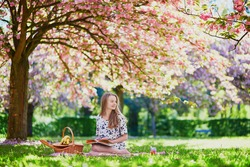 Girl having picnic and reading book in a beautiful cherry garden. Student preparing for exams or doing homework outdoors