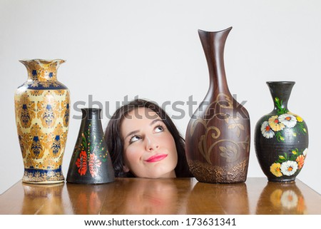 Girl head with vases on table admiring one of the vases