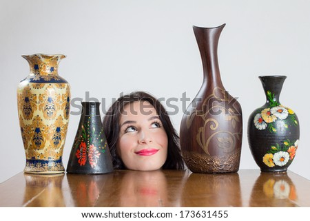 Girl head with vases on table smiling at one of the vases