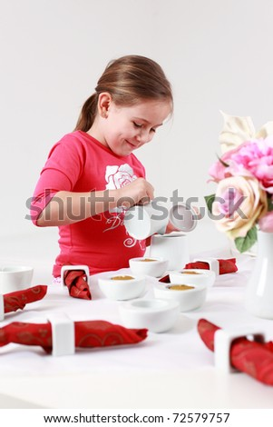 Girl helps to set the table - pouring tea