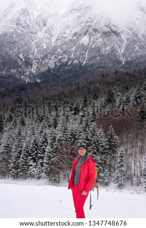 Girl hicking in the mountains during winter in the snow wearing a jacket and carrying a backpack. Active person in the cold weather