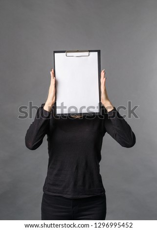 girl hides her face behind blank blank white sheet copy space for text