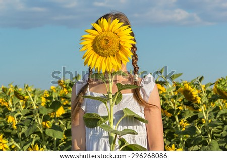 Girl hiding behind flower sunflower on a background of blue sky and field with sunflowers