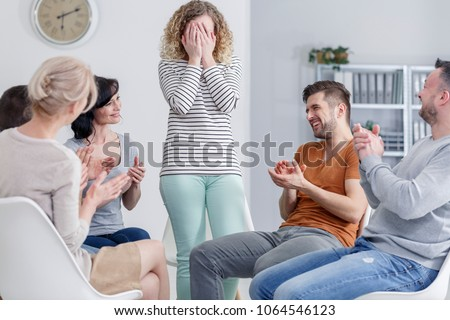 Girl hiding her face in her hands and happy people laughing and clapping in group psychotherapy