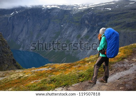 girl hiker are standing on a path and looking at the fjord