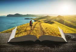 Girl hiker in a mountain valley on the pages of an open magical book. Majestic landscape. Travel and education concept.