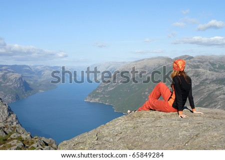 girl hiker sitting on a brink rock and looking at the mountains