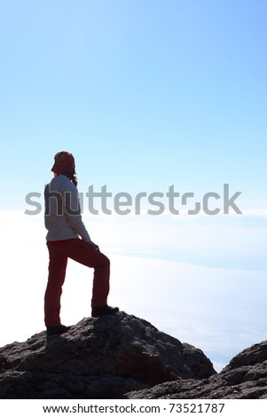 girl hiker standing on a rock and looking at the sea