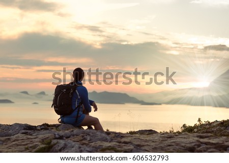 Girl hiking silhouette in mountains, sunset and ocean, fjords. Woman hiker with backpack on top of mountain looking at beautiful night landscape, fog in the mountains.