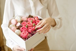 Girl hold a heart shaped box with fresh flowers pink roses and french sweets macarons in the hands.Female receive gift for mother's day,valentines,women day,birthday.Florist at work.close up.